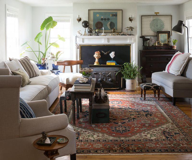Vintage globes on mantle in traditional living room.