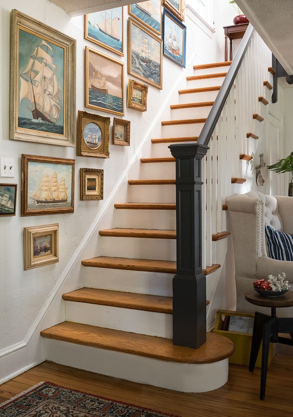 Nautical framed paintings on stairway wall.